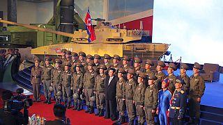 الزعيم الكوري الشمالي، كيم جونغ أون، يلتقط صورة جماعية مع الطيارين المقاتلين في افتتاح معرض لأنظمة الأسلحة في بيونغ يانغ، كوريا الشمالية، الإثنين 11 أكتوبر 2021