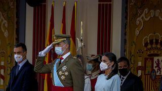 Spain's King Felipe salutes next to Queen Letizia and Prime Minister Pedro Sanchez.