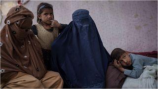 أمٌ أفغانية من ولاية قندوز (في الوسط)، تجلس مع أطفالها في مخيم للنازحين أثناء انتظارهم حافلة للعودة إلى ديارهم في كابول 9 تشرين الأول/أكتوبر 2021
