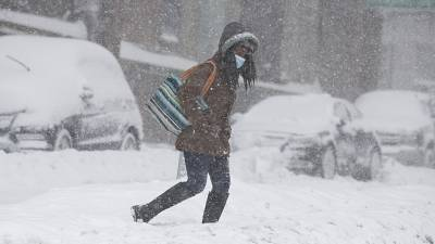 A woman crosses the street during a 2021 blizzard in New York.
