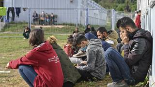 Migrants sit in front of containers at the Central Initial Reception Facility for Asylum Seekers, in Eisenhuettenstadt, Brandenburg, Germany, Oct. 6, 2021.