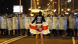 Tarihi Belarus bayrağı tutan bir protestocu polisin önünde duruyor. 9 Ağustos 2020