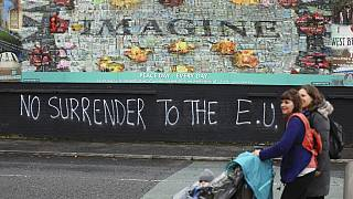 In this Monday Oct. 14, 2019 file photo people walk past pro-Brexit graffiti in West Belfast Northern Ireland.