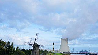 Gőz gomolyog egy atomerőműből egy régi szélmalom mellett a belgiumi Doelben