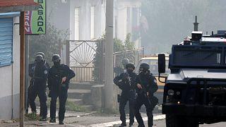ضباط شرطة كوسوفو يحرسون شارعًا في الجزء الشمالي الذي يسيطر عليه الصرب من بلدة ميتروفيتشا المنقسمة عرقياً في كوسوفو.