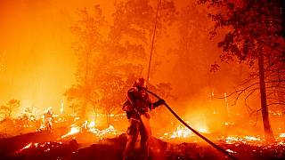 A firefighter douses flames as they push towards homes