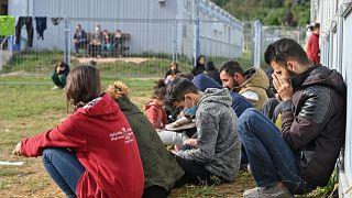Almanya'nın Brandenburg eyaletindeki sığınmacı kabul merkezinin önünde oturan göçmenler