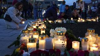 Flowers and candles were left after a man killed several people, in Kongsberg, Norway, Thursday, Oct. 14, 2021