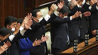 Japanese Prime Minister Fumio Kishida, center, and other lawmakers give three cheers after dissolving the lower house, the more powerful of the two parliamentary chambers.