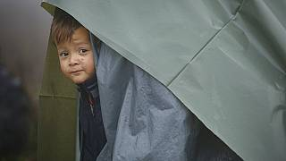 A migrant child peers from a makeshift tent at a camp housing migrants mostly from Afghanistan in Velika Kladusa, Bosnia, Tuesday, Oct. 12, 2021.