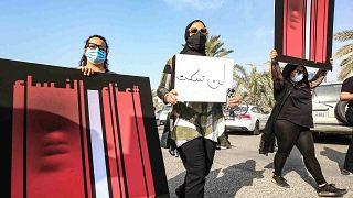 نساء كويتيات يحملن لافتة خلال مسيرة للتنديد بالعنف ضد المرأة، خارج مجلس الأمة، في العاصمة الكويتية، 22 أبريل 2021