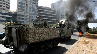 Lebanese army soldiers stand guard protesters burn garbage containers to block a road in Beirut.