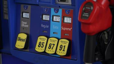 In this May 9, 2021, file photo prices are illuminated above the levers for the different grades of gasoline available at a pump at an Exxon station.