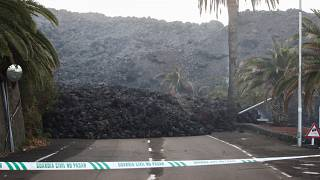 A Spanish Civil Guard tape is seen along a road blocked by lava spewed from the Cumbre Vieja volcano in La Laguna