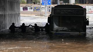 Passengers wade through high water after evacuating a bus stuck in a flooded underpass in southern Athens.