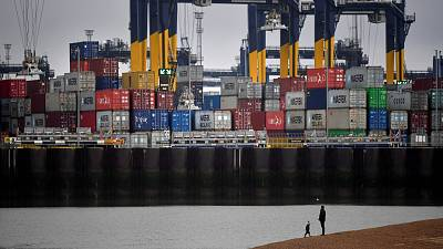 Shipping containers are seen as people walk on the beach near the Port of Felixstowe, east of London.