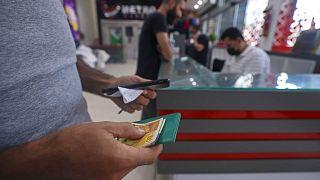 رجل فلسطيني يتلقى مساعدة مالية في سوبر ماركت في مدينة غزة كدعم من دولة قطر، 15 سبتمبر 2021