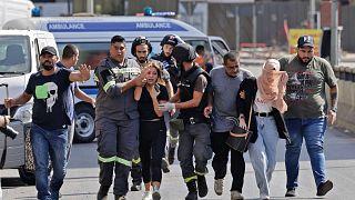 يساعد مسعفون لبنانيون في إجلاء المدنيين خلال الاشتباكات في منطقة الطيونة بالضاحية الجنوبية للعاصمة بيروت، 14 أكتوبر/تشرين الأول 2021