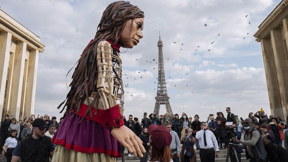 Este títere gigante camina en la piel de un joven refugiado que cruza Europa