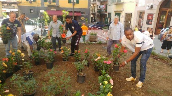 Residenti e migranti ripuliscono piazza