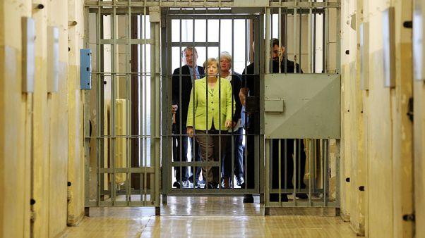 Merkel, visiting ex-Stasi jail, defends freedom and democracy