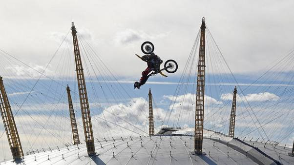 Daredevil backflips motorcycle between barges on London's Thames