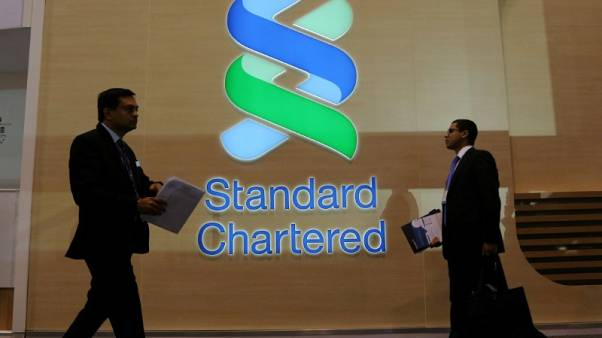 FILE PHOTO - People pass by the logo of Standard Chartered plc at the SIBOS banking and financial conference in Toronto, Ontario, Canada October 19, 2017. REUTERS/Chris Helgren/File Photo
