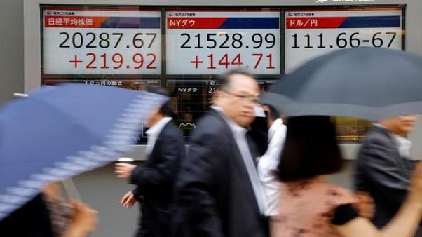 FILE PHOTO - People walk past an electronic board showing Japan's Nikkei average (L), the Dow Jones average (C), and the exchange rates between the Japanese yen and the U.S. dollar outside a brokerage in Tokyo, Japan June 20, 2017. REUTERS/Toru Hanai