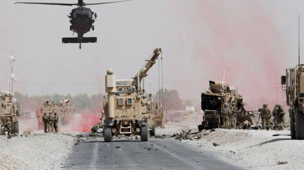 U.S. troops assess the damage to an armoured vehicle of NATO-led military coalition after a suicide bomber's attack in Kandahar province, Afghanistan August 2, 2017. REUTERS/Ahmad Nadeem