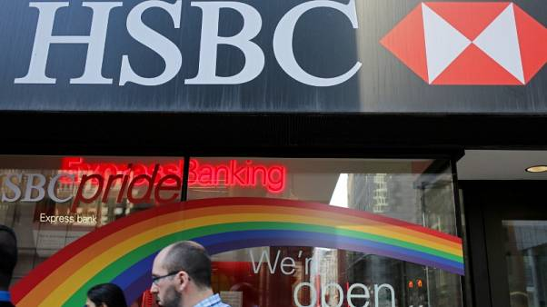 People pass by a branch of HSBC bank adorned in colours of the Pride rainbow flag symbolizing gay rights, in downtown Toronto, Ontario, Canada June 13, 2017. Picture taken June 13, 2017.  REUTERS/Chris Helgren