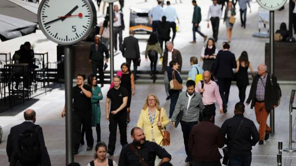 FILE PHOTO - People walk through the financial district of Canary Wharf, London, Britain 28 September 2017. REUTERS/Afolabi Sotunde