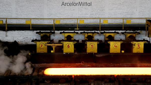 FILE PHOTO: A red-hot steel plate passes through a press at the ArcelorMittal steel plant in Ghent, Belgium, July 7, 2016. REUTERS/Francois Lenoir/File Photo