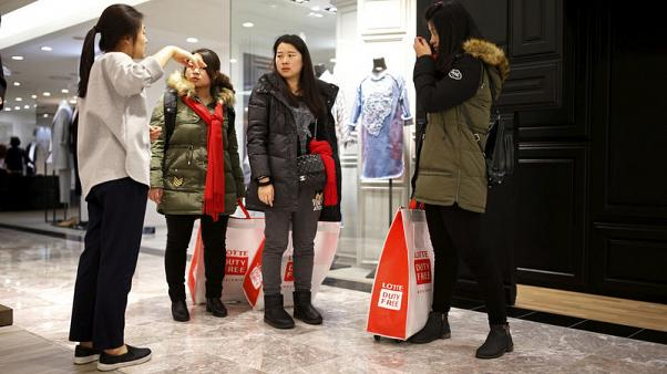 FILE PHOTO: Chinese tourists ask a sales assistant for directions at a Lotte department store in central Seoul, South Korea, February 2, 2016. REUTERS/Kim Hong-Ji/File Photo