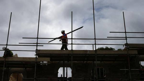FILE PHOTO - A builder assembles scaffolding as he works on new homes, in south London June 3, 2014.   REUTERS/Andrew Winning/Files