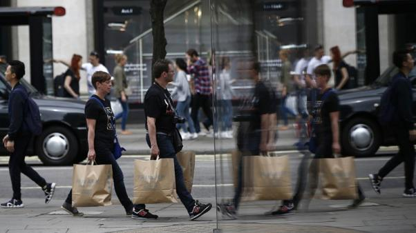 FILE PHOTO - Shoppers are reflected in a window as they walk along Oxford Street in London, Britain July 9, 2016. Picture taken July 9, 2016.  REUTERS/Peter Nicholls