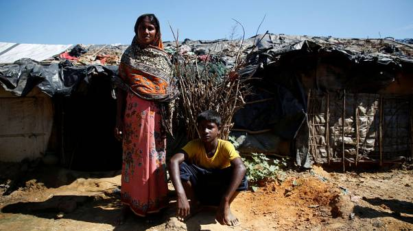 Zuhura Begum, 30, a Rohingya refugee, poses for a picture with her son Anwar Hossain, 12, outside their temporary shelter at Kutupalong refugee camp near Cox's Bazar, Bangladesh, November 12, 2017. REUTERS/Navesh Chitrakar