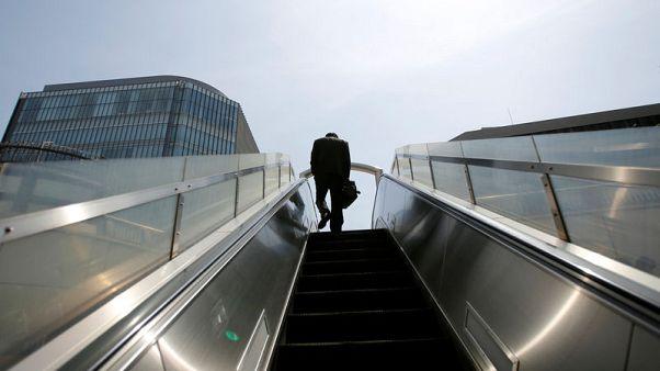 FILE PHOTO: A businessman rides on an escalator in Tokyo's business district April 1, 2013.   REUTERS/Toru Hanai/File Photo
