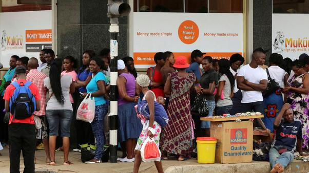 FILE PHOTO: People queue to withdraw money from a bank in Harare, Zimbabwe's capital, March 8, 2017. REUTERS/Philimon Bulawayo/File Photo