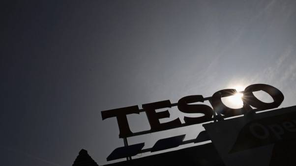 FILE PHOTO - The signage of Tesco Extra is silhouetted against the sun in southwest London September 22, 2014. REUTERS/Luke MacGregor
