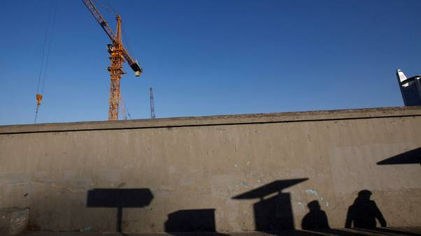 FILE PHOTO: Pedestrians cast their shadows  on a wall at a construction site in Beijing December 12, 2014. REUTERS/Kim Kyung-Hoon/File Photo