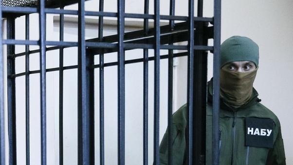 FILE PHOTO - A member of the National Anti-Corruption Bureau of Ukraine stands guard next to a defendants' cage during a court hearing in Kiev, Ukraine April 21, 2017. Picture taken April 21, 2017. REUTERS/Valentyn Ogirenko