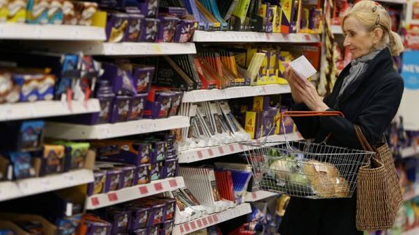 FILE PHOTO: A shopper checks her shopping list in a supermarket in London, Britain April 11, 2017.  REUTERS/Neil Hall/File Photo