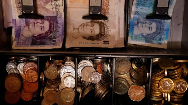 Pound notes and coins are seen inside a cash register in a bar in Manchester, Britain September 6, 2017. REUTERS/Phil Noble