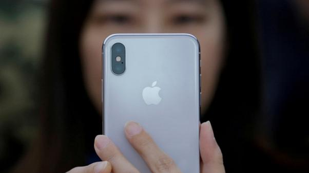 FILE PHOTO: A attendee uses a new iPhone X during a presentation for the media in Beijing, China October 31, 2017. REUTERS/Thomas Peter/File Photo