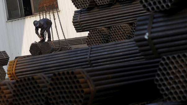 FILE PHOTO - A worker ties a pile of steel pipes on a crane at the yard of a steel pipe plant in Tangshan in China's Hebei Province November 3, 2015. REUTERS/Kim Kyung-Hoon/File Photo