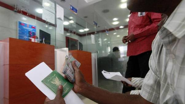 رجل يحمل جواز سفره وينتظر تحويل أموال الى عملة أجنبية في مكتب صرافة في الخرطوم. صورة من أرشيف رويترز.