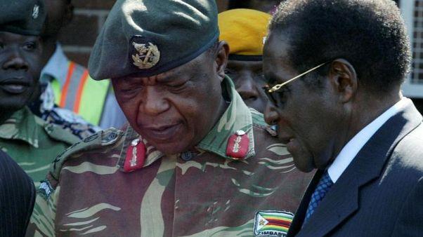 رئيس زيمبابوي روبرت موجابي يتحدث مع قائد القوات المسلحة كونستانتينو تشيونجا في هاراري. صورة من أرشيف رويترز.
