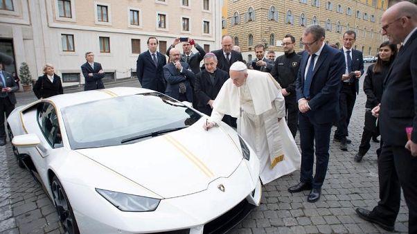البابا فرنسيس يوقع على سيارة لامبورجيني في ساحة القديس بطرس في الفاتيكان يوم الأربعاء. (صورة حصلت عليها رويترز لا يحوز اعادة بيعها).