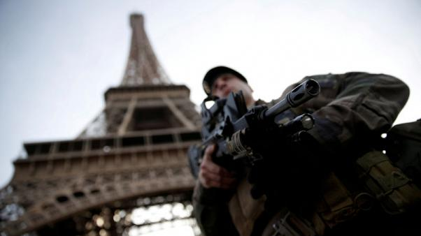 FILE PHOTO: A French soldier stands guard under the Eiffel Tower, as France officially ended a state of emergency regime, replacing it with the introduction of a new security law, in Paris, France, November 1, 2017. REUTERS/Christian Hartmann