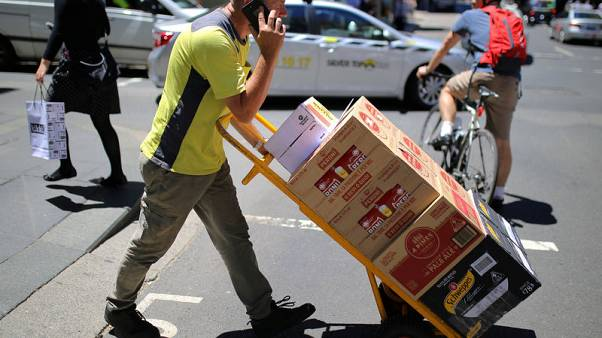 A worker talks on his phone as he pushes a trolley loaded with goods across a main road in a retail shopping area in central Sydney, Australia, November 15, 2017.  REUTERS/Steven Saphore